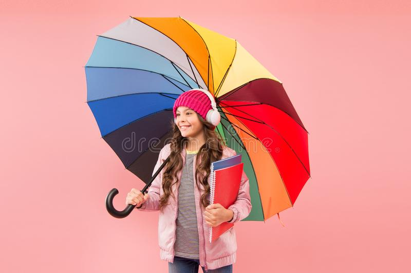 Every day fun. Child enjoying simple things. Entertain yourself. Fun concept. Feeling good. Girl having fun walking. Wireless headphones under colorful umbrella stock photo