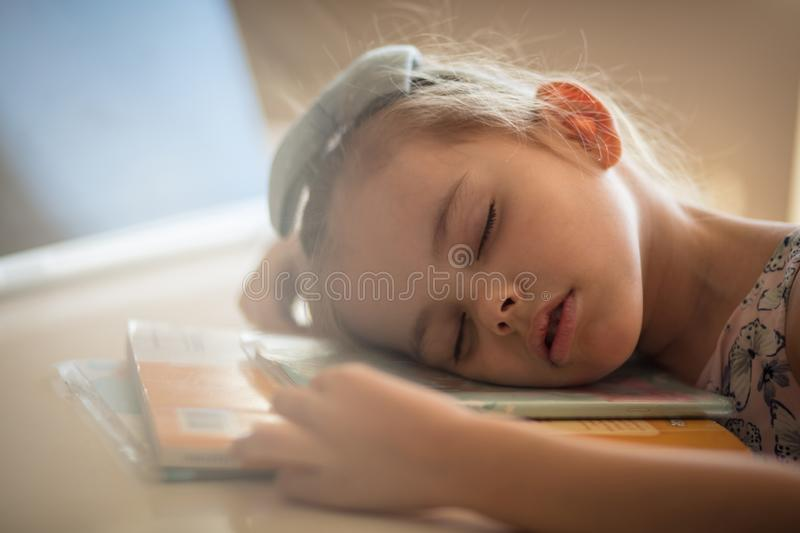 Every learning should be moderate. Little girl sleeping. Close up royalty free stock photo