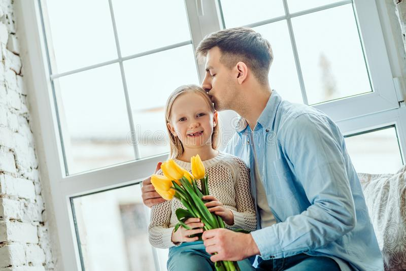 Every moment with her is precious. Daughter and father sitting together on the windowsill at home. Little kid holding bouquet of royalty free stock image