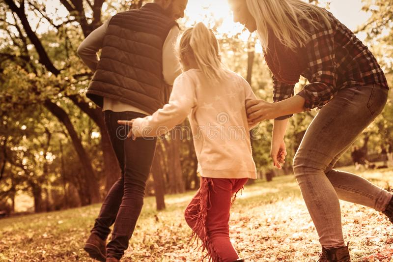 Every moment spent together is absolute bliss. Cheerful family with one child playing together in park stock images