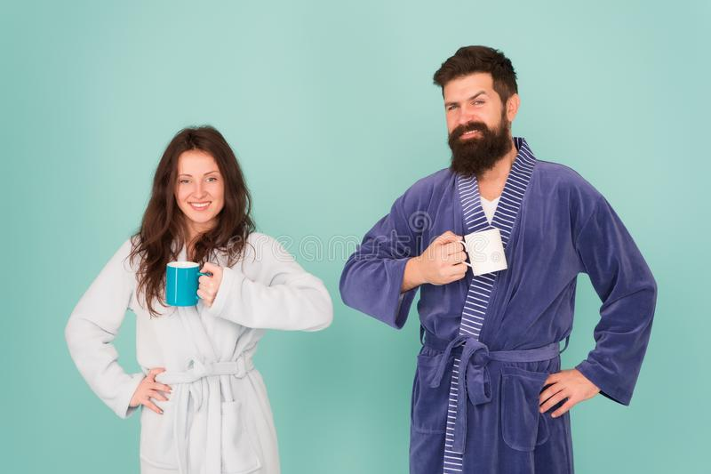 Every morning begins with coffee. Couple in bathrobes with mugs. Man with beard and sleepy woman enjoy morning coffee or royalty free stock image