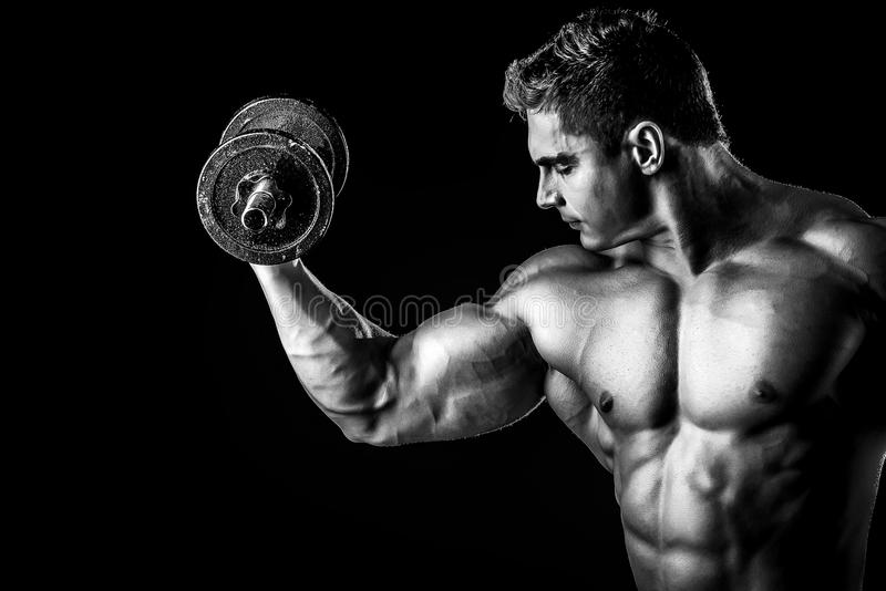 Every muscle. Portrait of a handsome muscular bodybuilder posing with dumbbells over black background stock photo