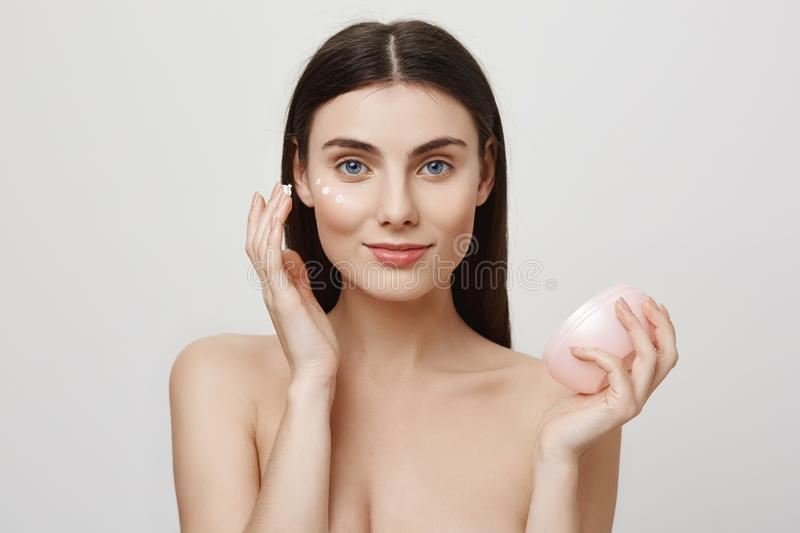 Every natural beauty needs some help. Portrait of charming blue-eyes european girl putting on facial cream, rubbing it stock photography