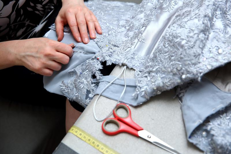 A woman embroidering a handmade dress. Today, tailoring can be called as an artistic profession. Every tailor shop, even the most modern one, will not be able stock image