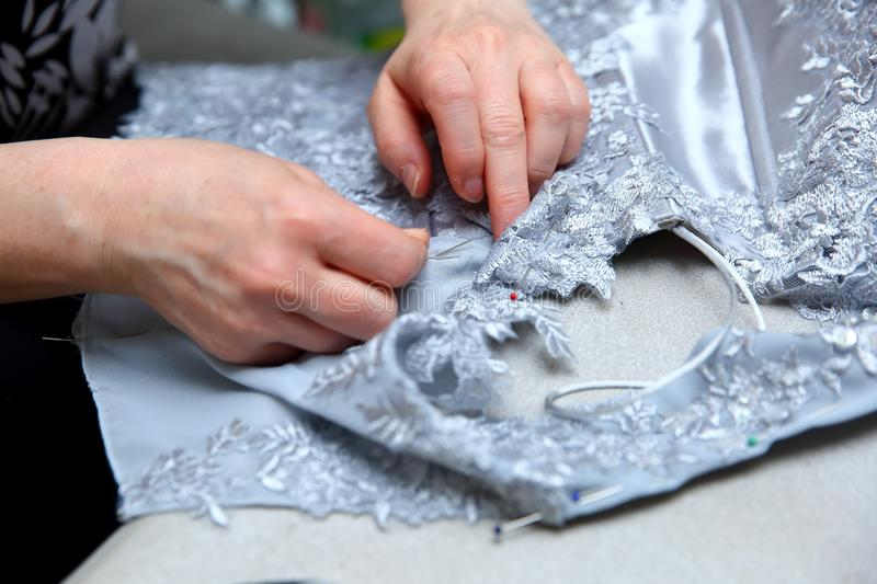 A woman embroidering a handmade dress. Today, tailoring can be called as an artistic profession. Every tailor shop, even the most modern one, will not be able royalty free stock photos