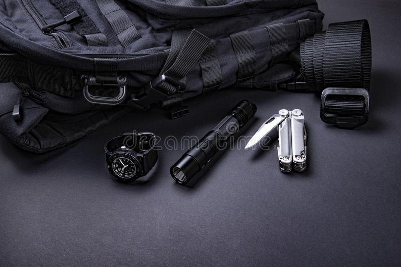 Everyday carry EDC items for men in black color - backpack, tactical belt, flashlight, watch and silver multi tool. stock image