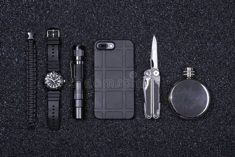 Everyday carry EDC military items for men- multi tool, lighter, phone, tactical watch, survival bracelet,flashlight and flask. stock photos
