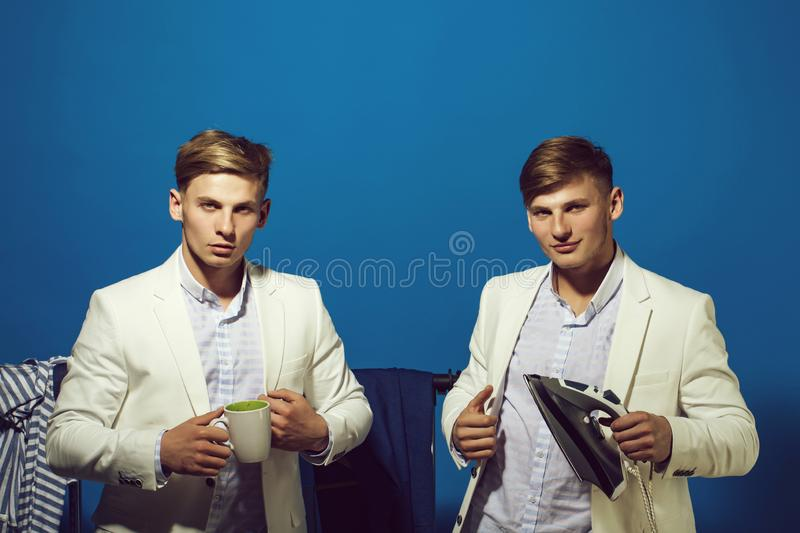 Everyday life and housework. Housekeeping and household. Guys smiling in wardrobe with morning cup. Men twin in jacket hold iron. Macho ironing clothes royalty free stock photos