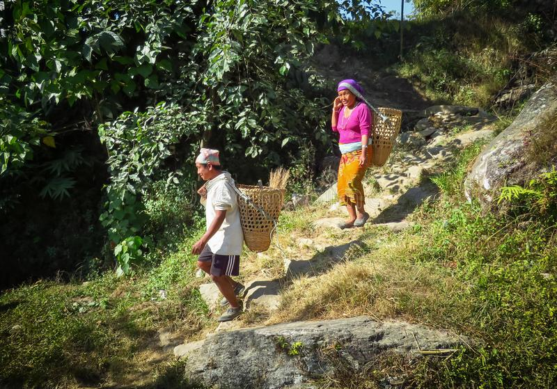Everyday life in remote mountain areas of Nepal, workers carrying baskets. Gairi Pangma, Sankhuwasabha District, Nepal - 11/19/2017: Every day life of Nepalese royalty free stock images