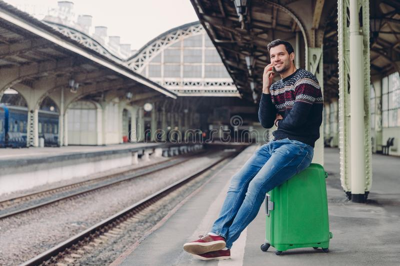 Everyday lifestyle concept. Handsome man wears sweater and jeans, poses at rail station platform, leans at bag, has telephone stock photography