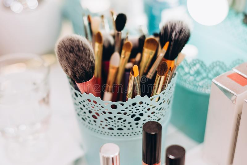 Visa brushes in a turquoise vase stand on the table royalty free stock images