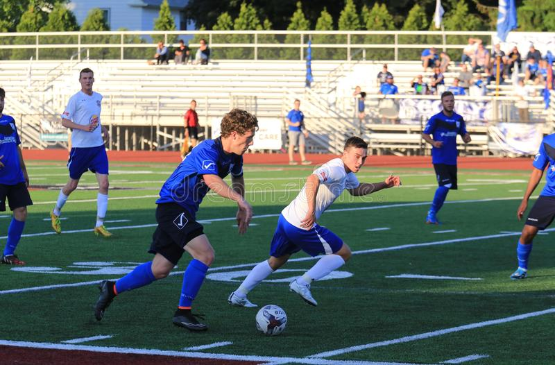 Everyone congregates for the loose soccer ball. Defender rushes to slow the offense at the professional Soccer event, pro football game, NPSL, National Premier royalty free stock image