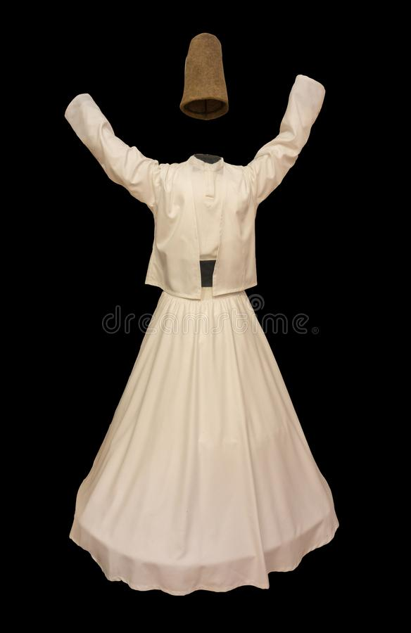 Whirling Dervish Costume against Black Background. Everyone is familiar with the image of the whirling dervish, clad completely in white and spinning expertly as royalty free stock photo