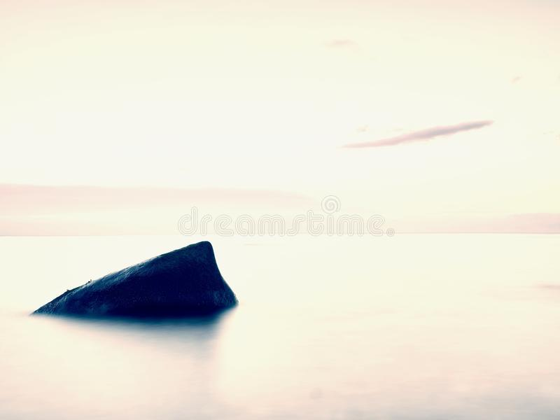 Everyone loves romantic atmosphere of sea. Peaceful sea level, stones in water. Everyone loves romantic atmosphere of sea. Peaceful morning sea level with stones royalty free stock photography