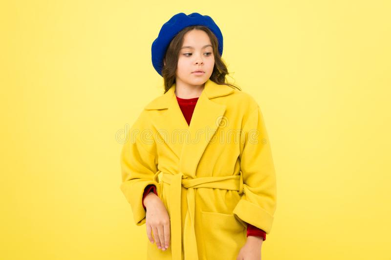 Everyone needs coat this winter. Girl fashionable cute model wear yellow wool coat. Pensive child in warm clothes. Personal styling and bespoke tailoring stock image