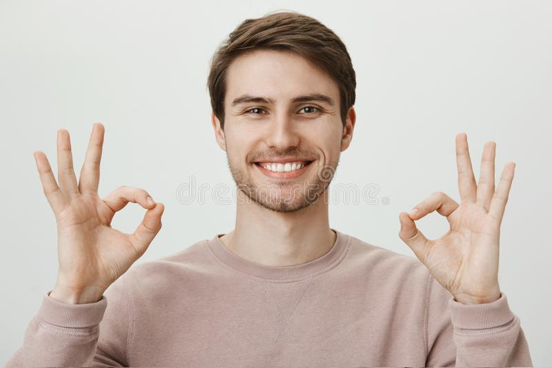 Everything is awesome. Portrait of satisfied good-looking mature caucasian guy with bristle showing okay or fine gesture. With both hands, telling that he feels royalty free stock photo