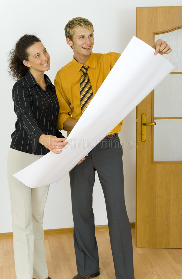 Everything is correct!. Young, happy designers couple holding plans. Standing in flat's room. Looking at something royalty free stock images