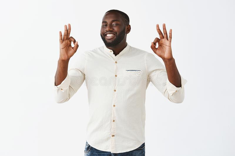 Everything is excellent. Satisfied attractive african american male businessman in white shirt showing okay or ok royalty free stock images