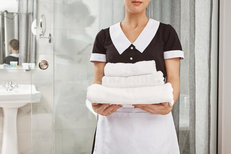 Everything is fresh and clean. Cropped portrait of housecleaner in maid uniform holding pack of white towels. Employee stock photography