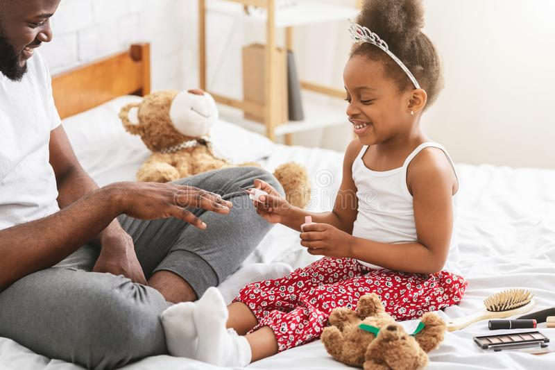 Cheerful black girl making manicure for daddy stock photo