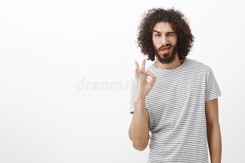 Everything pod kontrolnym niemowlęciem Przystojny ufny latynoski mężczyzna z brodą, kędzierzawą fryzurą i ok znakiem, pokazywać o zdjęcia stock
