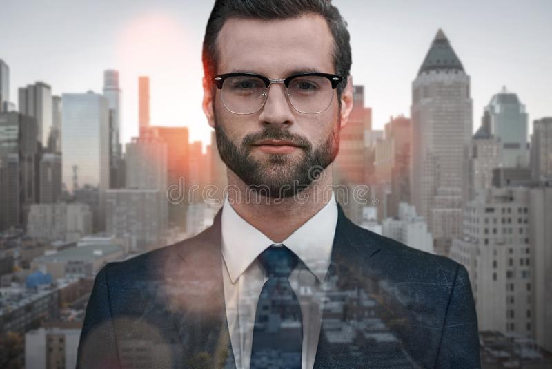 Everything should be perfect. Close-up of young successful businessman looking at camera standing outdoors with. Cityscape on the background. Business look stock photo