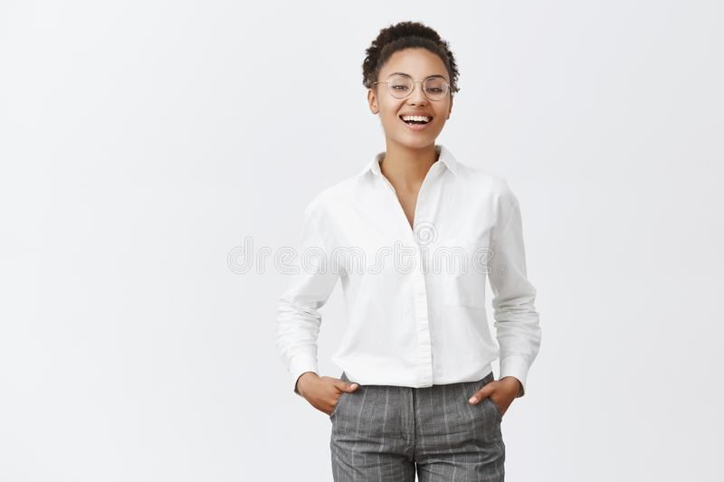 Everything under control. Good-looking african female in glasses, shirt and pants, holding hands in pockets, smiling and stock images