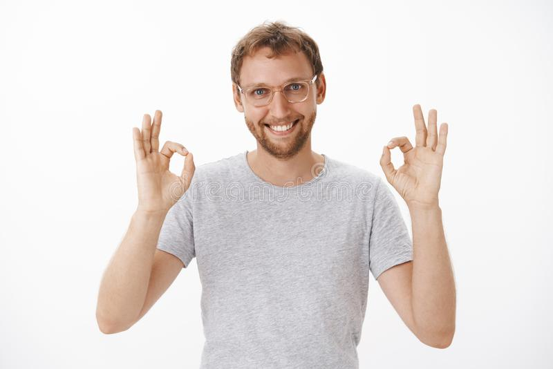 Everything under control trust me. Portrait of pleased friendly and self-assured handsome bearded man in glasses raising royalty free stock image