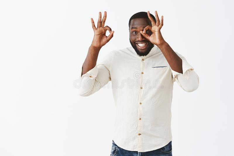 Everything will be excellent, guarantee you. Joyful friendly and pleasant african american man in white shirt making royalty free stock photography