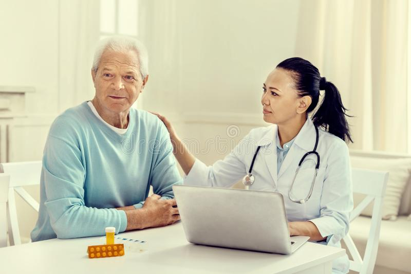 Careful female nurse calming sad elderly patient royalty free stock photography