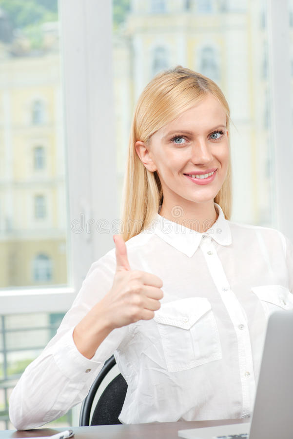 Everything is wonderful! Young pretty office worker sitting at a royalty free stock photo