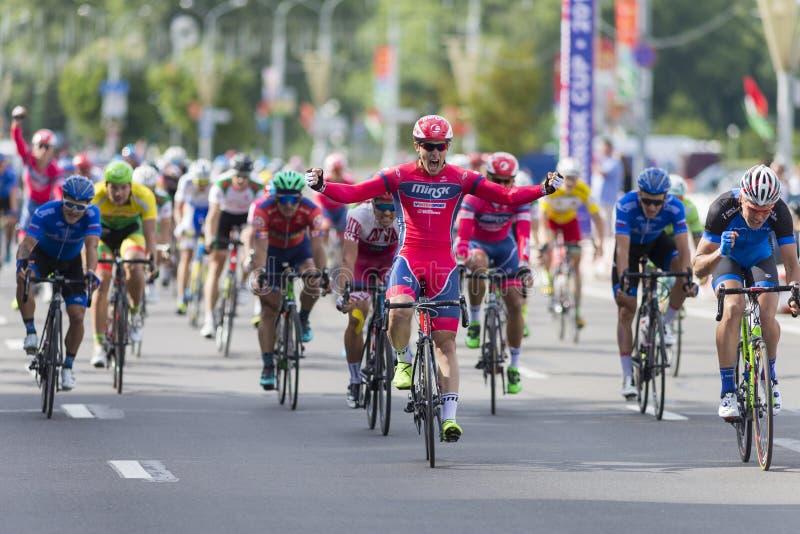 Evgeny Korolek du Belarus croisant la ligne d'arrivée devant le Peloton pendant la concurrence de recyclage Grand prix de route i image libre de droits