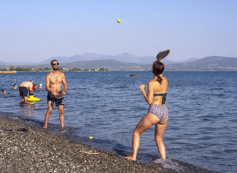 Evia海岛,希腊 2019年7月:演奏在海滩的男孩和女孩frescobol -海滩网球-木球拍和球在晴朗的su 库存图片