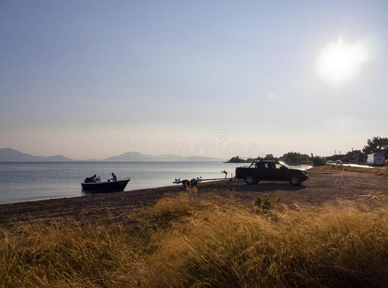 Evia Island, Greece. July 2019: Fishermen brought a boat on a trailer by car at sunset in the Aegean sea. Evia Island, Greece. July 2019: Fishermen brought a royalty free stock photo