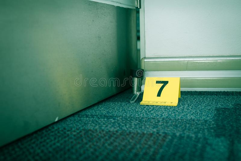 Evidence marker number 7 on carpet floor near suspect object in royalty free stock photography