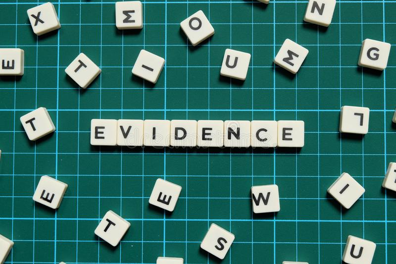 Evidence word made of square letter word on green square mat background. Evidence word made of square letter word on green square mat background stock photos