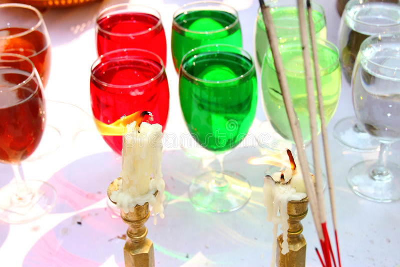 Evil candles burning and color water in glasses background. In Black magic ritual or scary halloween rite stock photography
