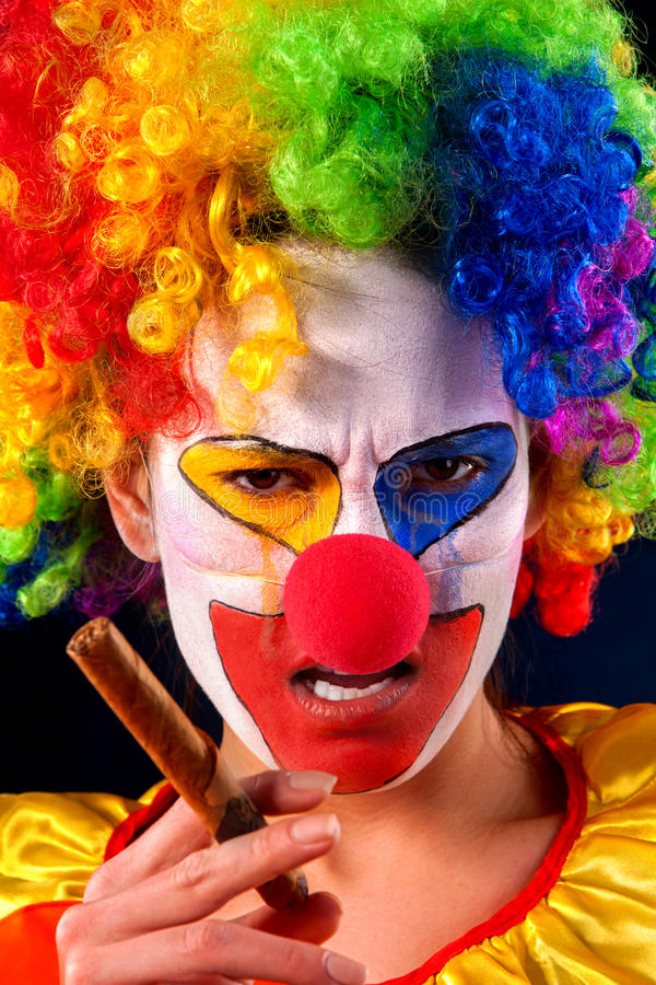 Evil clown on black background. Portrait of smoke woman. Evil clown on black background. Mad woman is smoking cigar. Portrait of crazy female with an angry look royalty free stock images