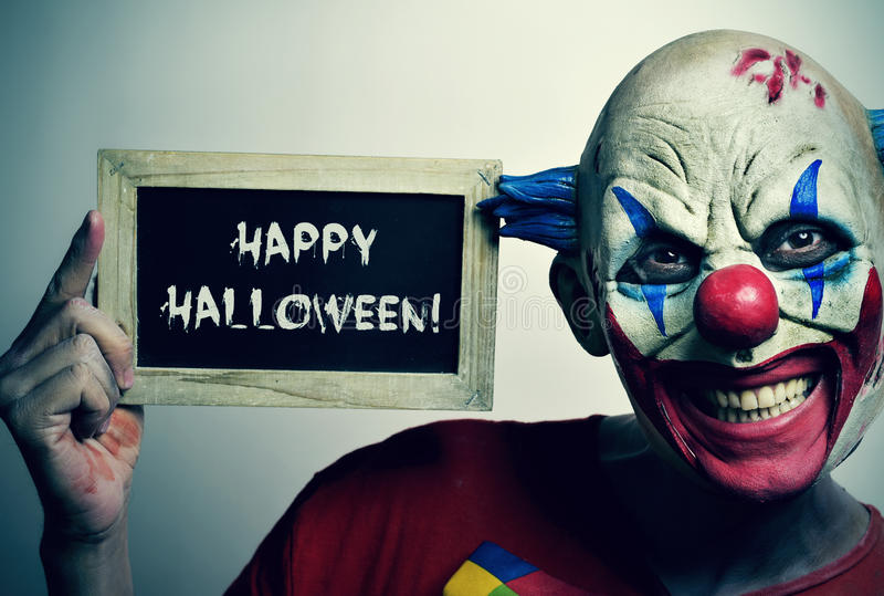 Evil clown with a chalkboard with the text happy Halloween. Portrait of a scary evil clown with a chalkboard with the text happy Halloween written in it royalty free stock photos