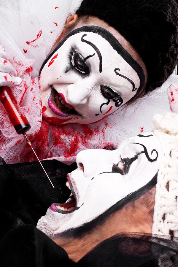 Evil Clown with syringe threatened another clown. Female evil Clown with syringe threatened male clown royalty free stock image