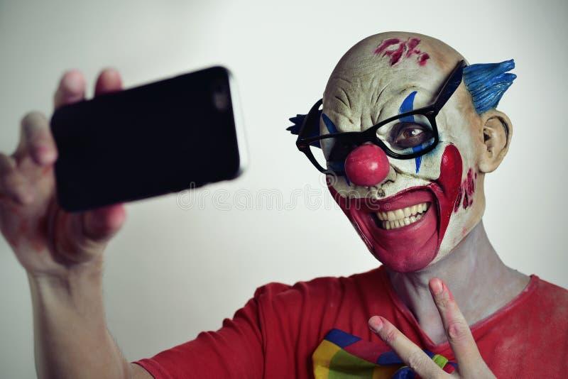 Evil clown taking a selfie stock images