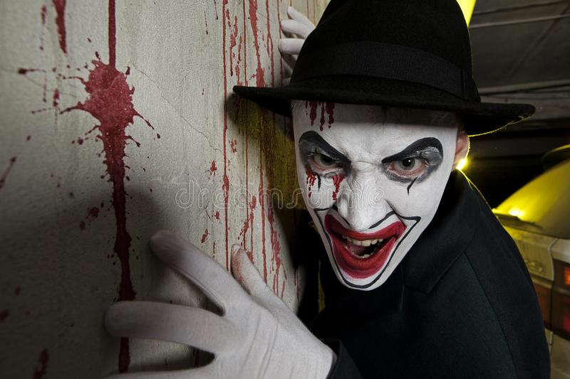Evil clown wearing a bowler hat on wall royalty free stock images