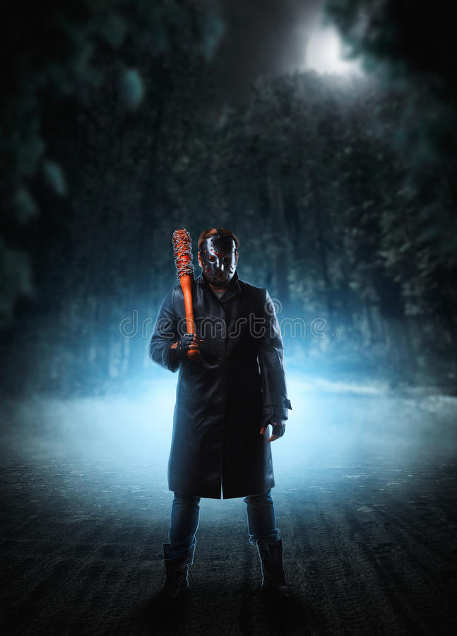 Evil embodiment in hockey mask and leather coat stock image