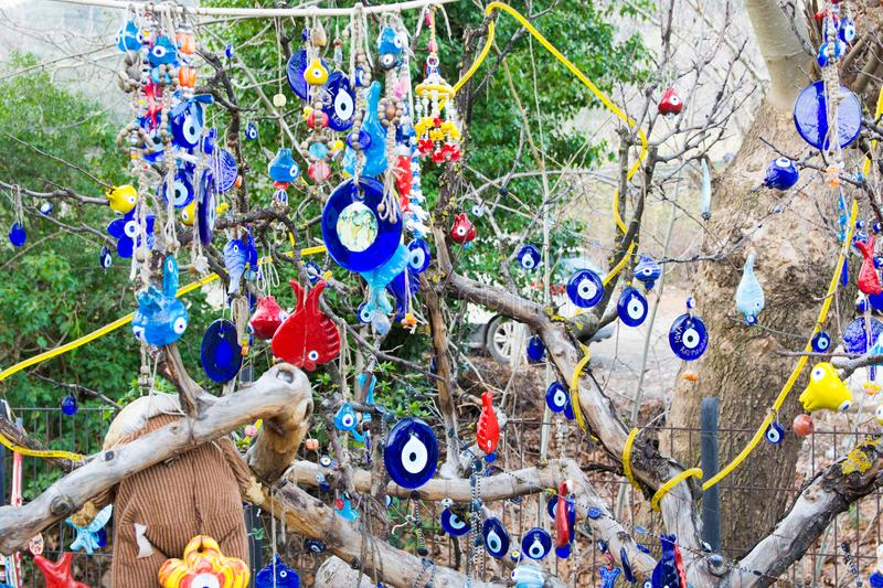 Evil Eye Bead. Wish Tree. Evil eye bead souvenirs.broken glass is melted and shaped. In culture and religious belief, the figure of the eye is regarded as a stock photography