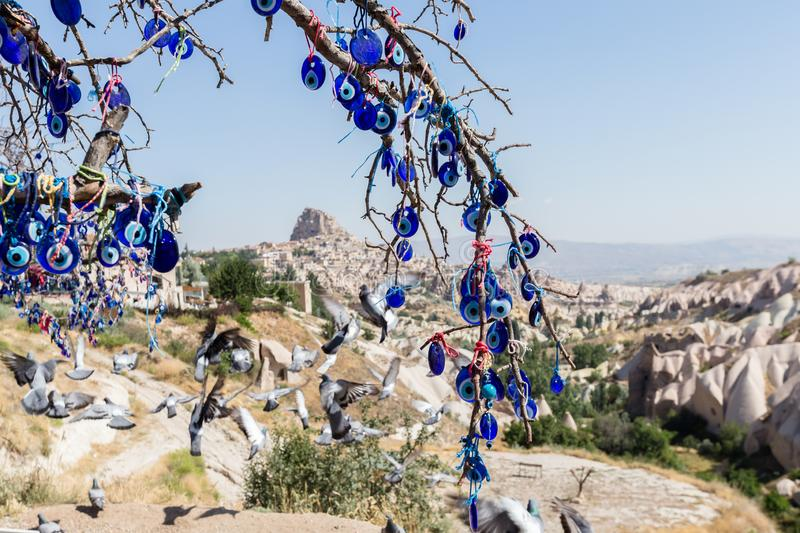 Evil Eye Beads on Tree and Fairy tale chimneys in Guvercinlik Valley. Branches of old tree decorated with the eye-shaped amulets,Nazars,Evil eye stock image