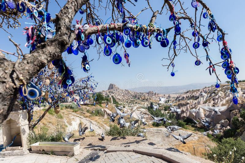 Evil Eye Beads on Tree and Fairy tale chimneys in Guvercinlik Valley. Branches of old tree decorated with the eye-shaped amulets,Nazars,Evil eye stock photos