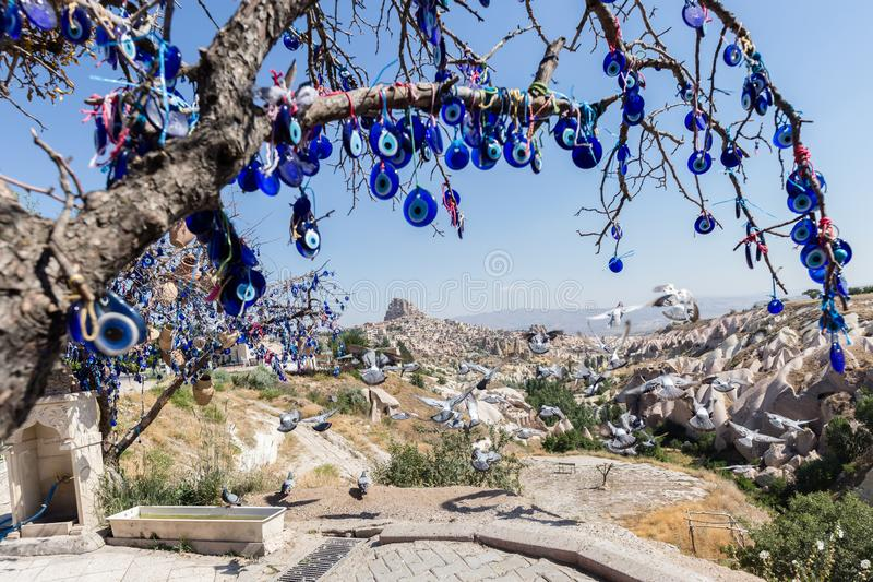 Evil Eye Beads on Tree and Fairy tale chimneys in Guvercinlik Valley. Branches of old tree decorated with the eye-shaped amulets,Nazars,Evil eye royalty free stock image