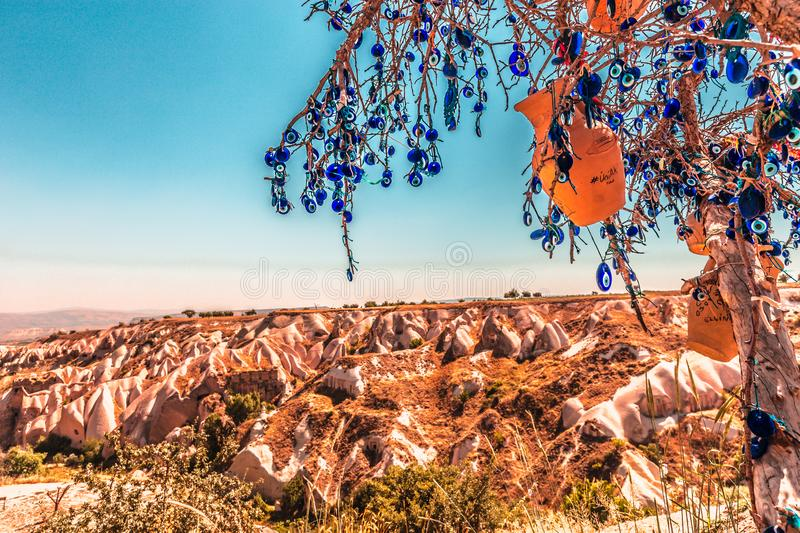 Evil Eye Beads on Tree and Fairy tale chimneys in Guvercinlik Valley. Branches of old tree decorated with the eye-shaped amulets,Nazars,Evil eye royalty free stock photos