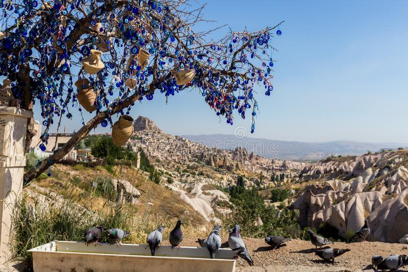 Evil Eye Beads on Tree and Fairy tale chimneys in Guvercinlik Valley. Branches of old tree decorated with the eye-shaped amulets,Nazars,Evil eye stock images