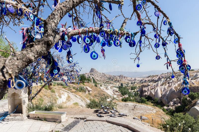 Evil Eye Beads on Tree and Fairy tale chimneys in Guvercinlik Valley. Branches of old tree decorated with the eye-shaped amulets,Nazars,Evil eye royalty free stock photography